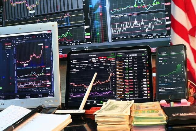 graphs-charts-displayed-on-monitors-and-pile-of-money